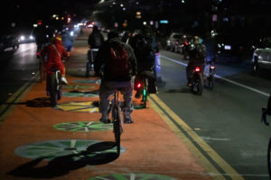 Group of 20 cyclists riding at night on wide road, with center lane painted orange with colorful wheel graphics. The cyclists are taking the right and center lanes. Lights of cars are seen both approaching and going away.